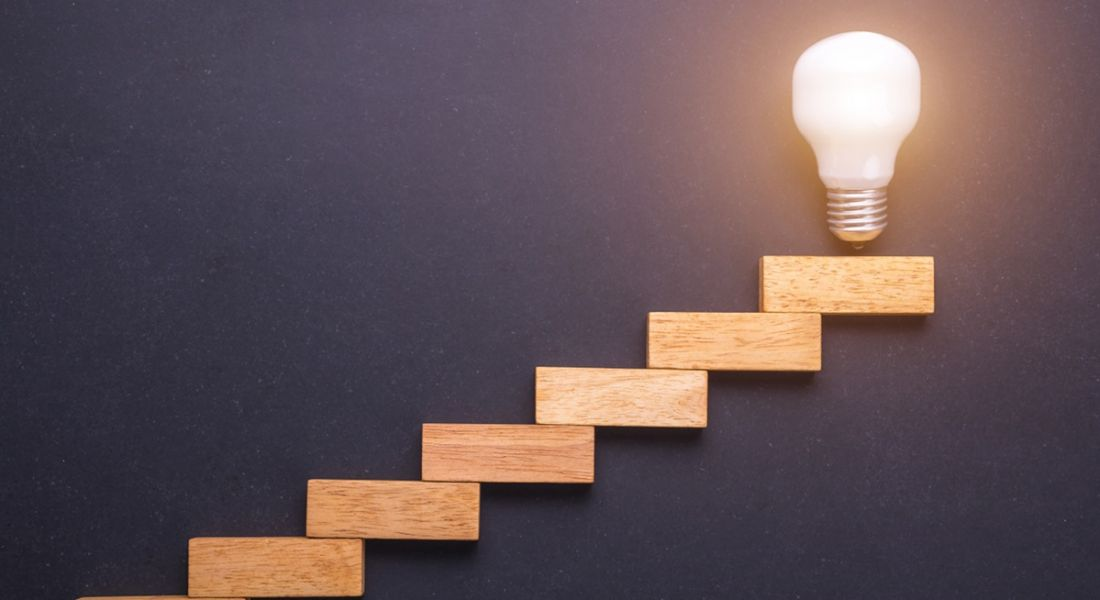Wooden blocks set up as a staircase with light bulb on the top, in front of black stone board.