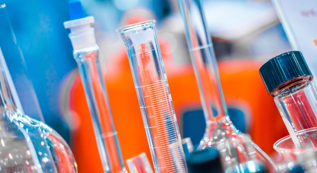 Close-up view of beakers crowded on a table in a life sciences lab.