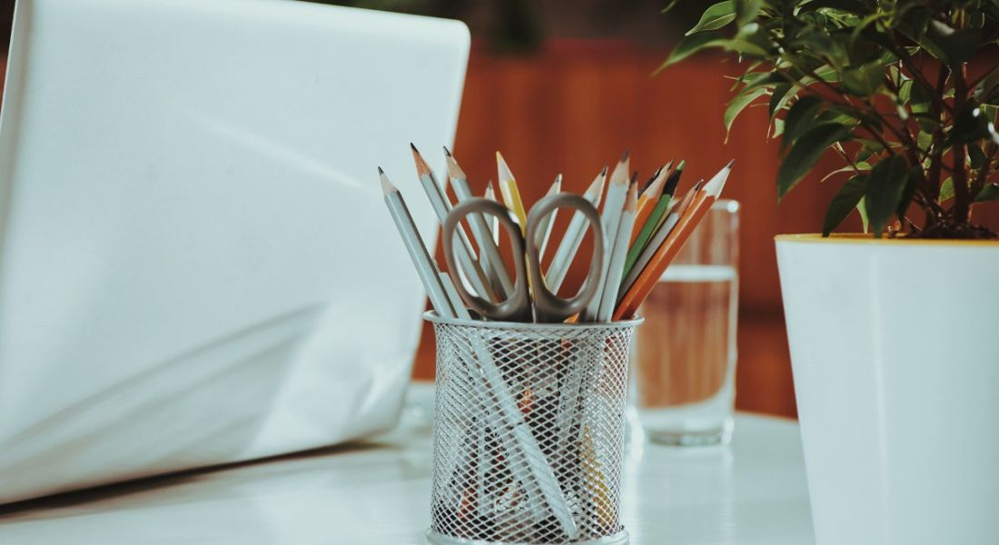 View of pencils on a desk next to a laptop in a modern office.