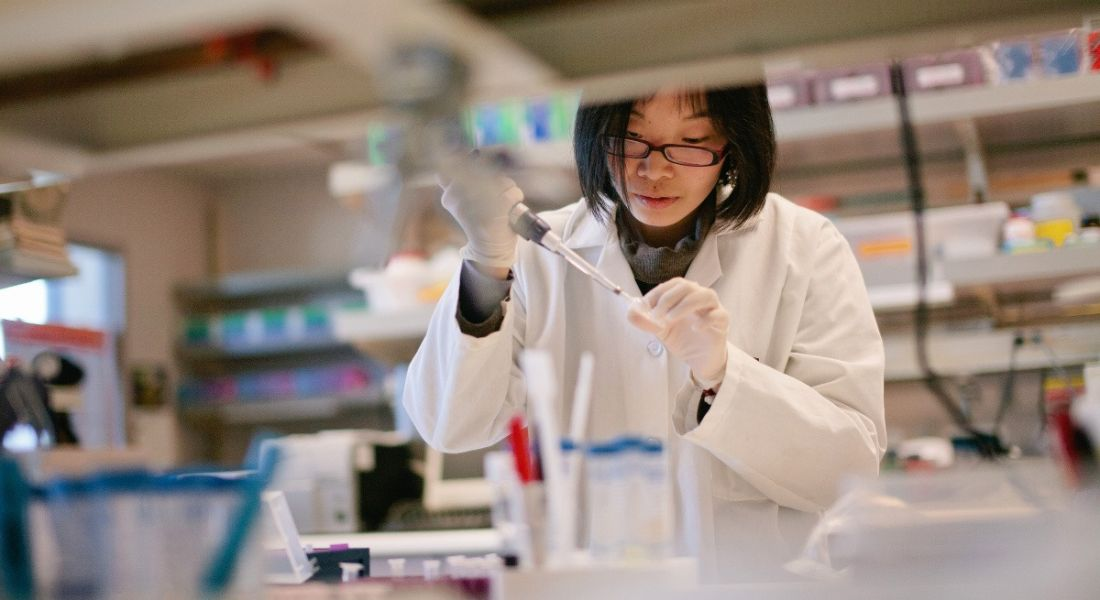 A woman in a white lab coat wearing disposable gloves can be seen pipetting in a lab from across a bench busy with equipment and test tubes.