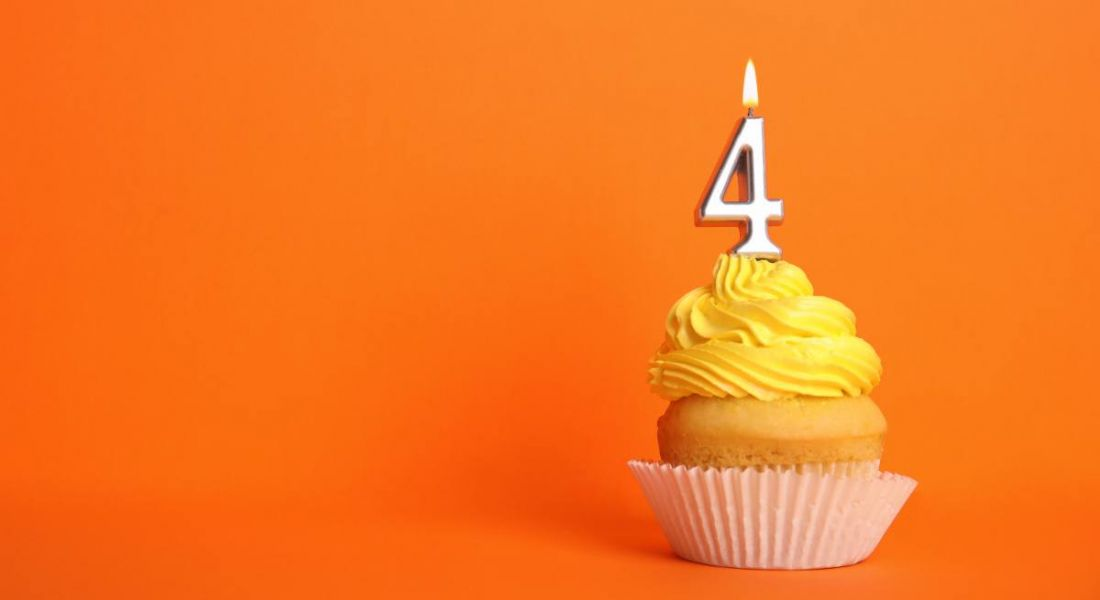 Birthday cupcake with number four candle on orange background.