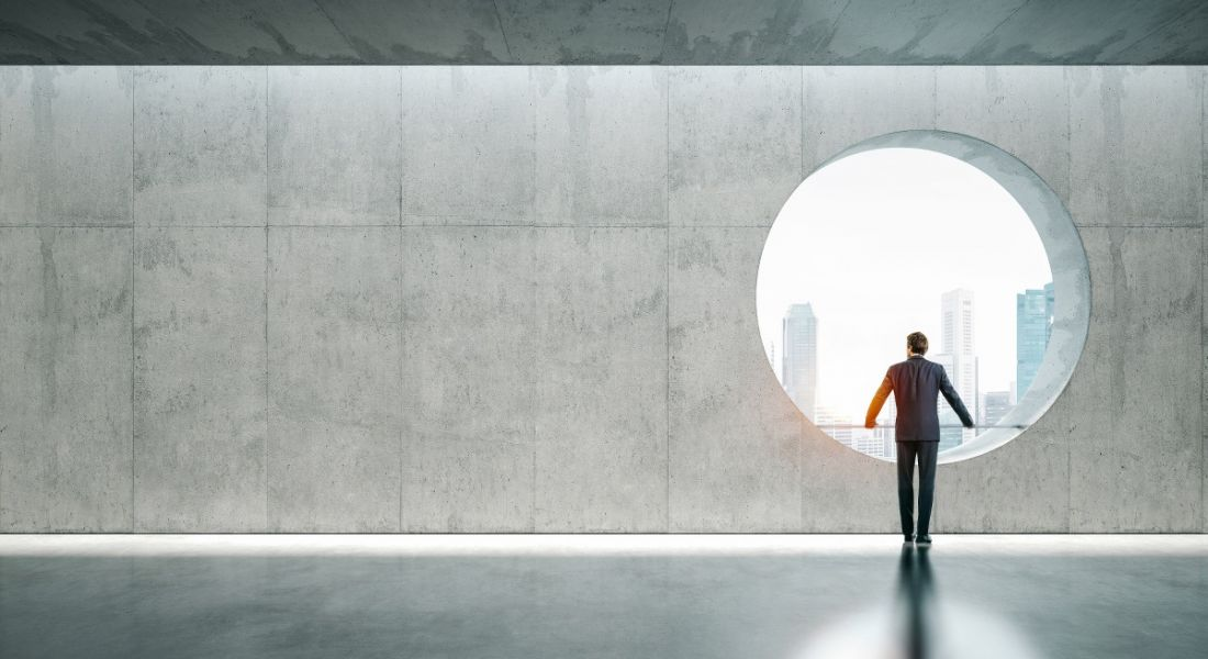 A man stands in a futuristic hallway looking out a large circular window to the city.
