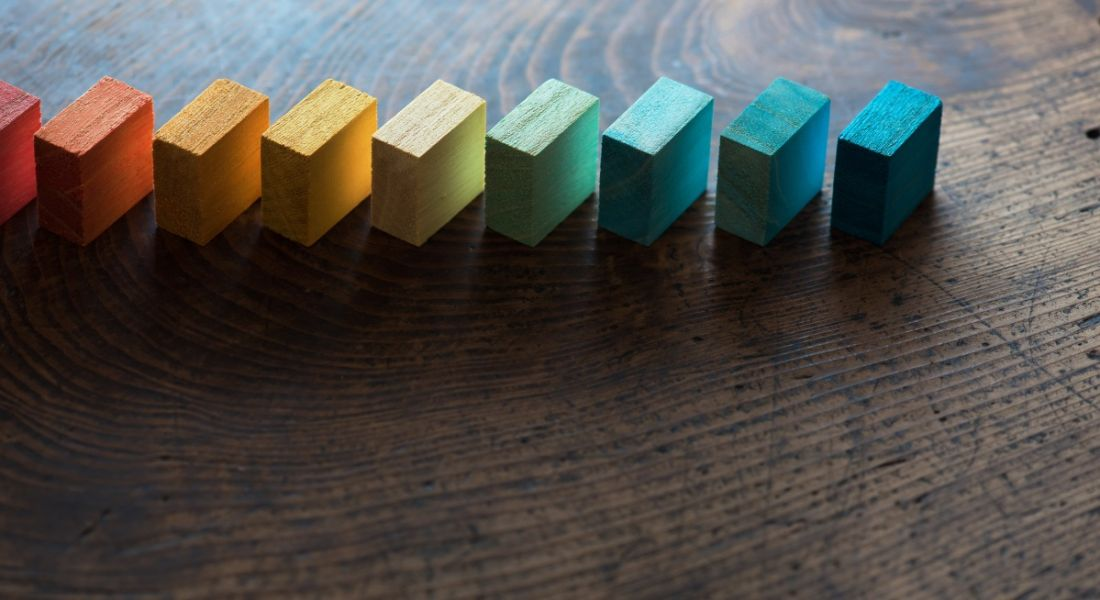 Coloured wooden blocks diagonally aligned on an old vintage wooden table.