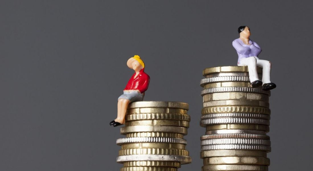 Concept of small figurines of a woman sitting on a smaller pile of coins beside a man on a larger pile of coins.