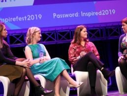 Ciara-Beth Griffin onstage at Inspirefest wearing a white cardigan and a red dress.