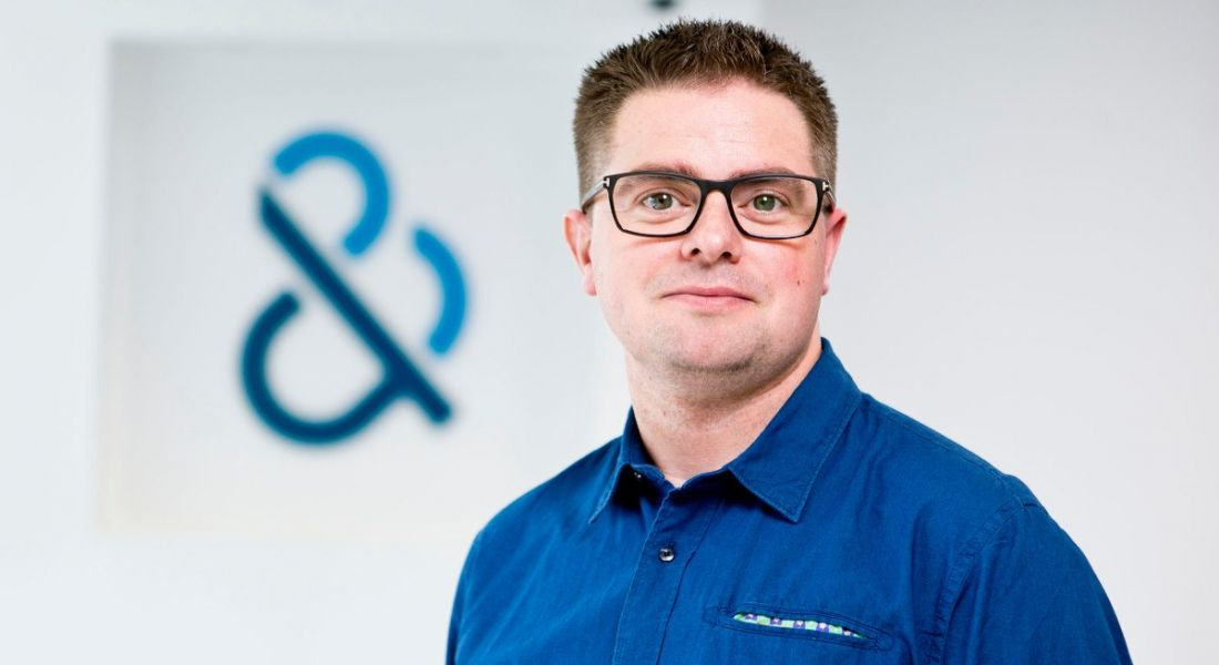 Corporate headshot of a man with glasses and a blue shirt in an office.