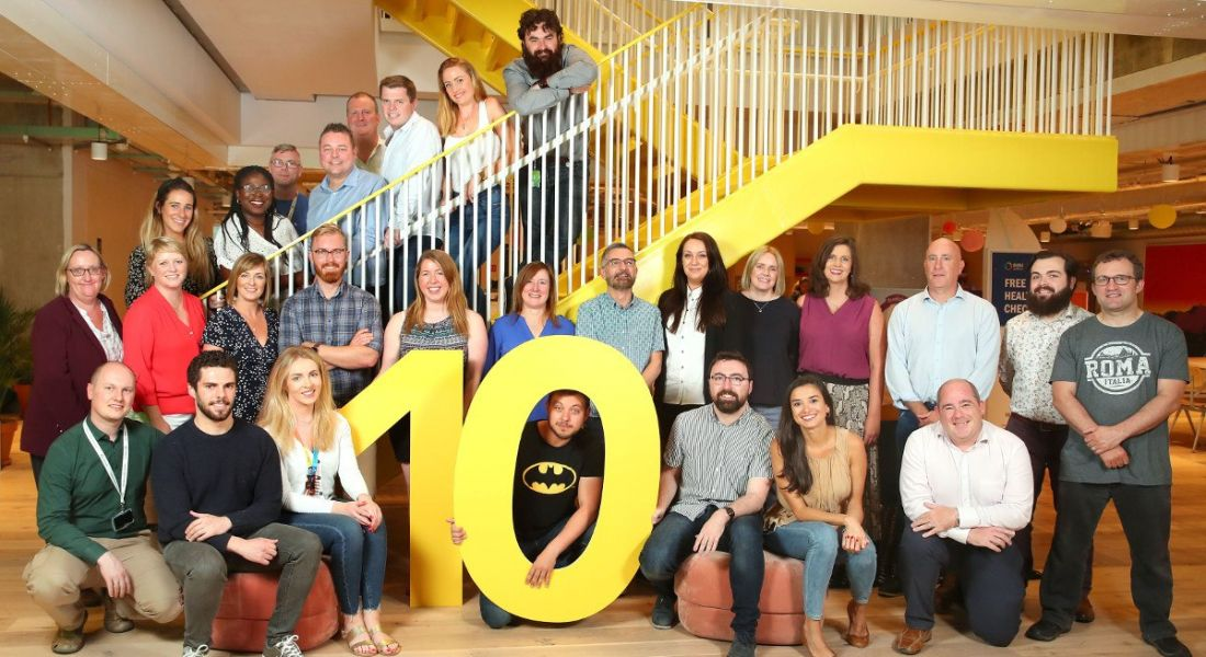Singlepoint staff members gathered on a flight of stairs around a large yellow figure 10.