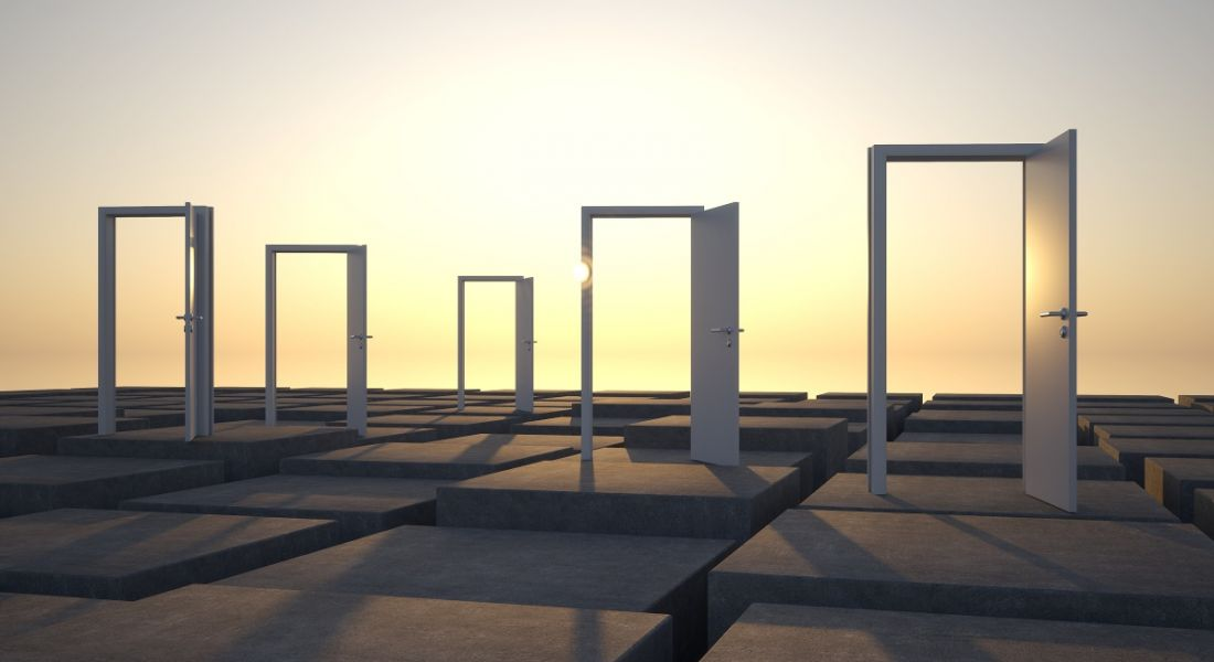 Abstract photo of open doors in an outdoor setting with sun rising behind them.