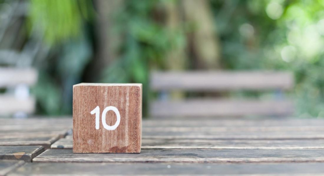 Wooden cube engraved with the number 10 in white paint, sitting on a natural bench with blurred trees in the background.