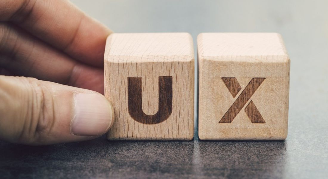 Two cubed wooden blocks with the letters U and X on them, sitting on a grey surface,.