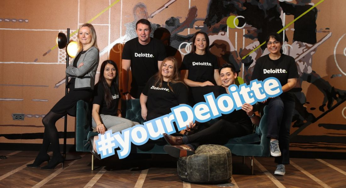View of young people in Deloitte T-shirts holding 'Your Deloitte' sign.