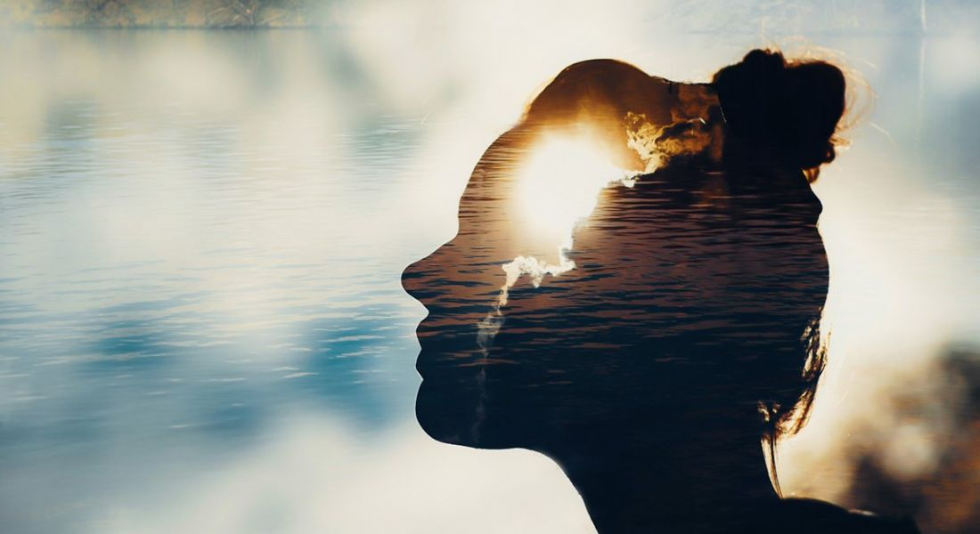 Abstract picture of a female silhouette with the sun shining through her head and a bright, cloudy sky in the background.