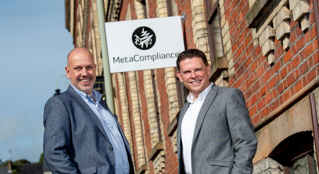 Two men in business attire standing outside Georgian building on sunny day with sign above saying MetaCompliance.