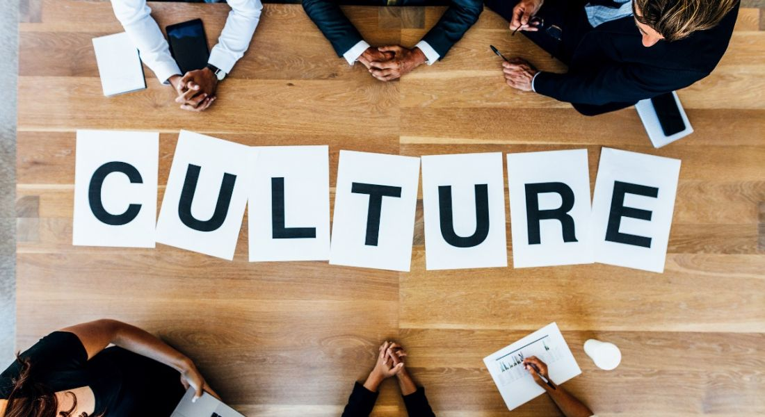 Group of business people with alphabet signs forming the word culture on the table. Top view of business people in a meeting.