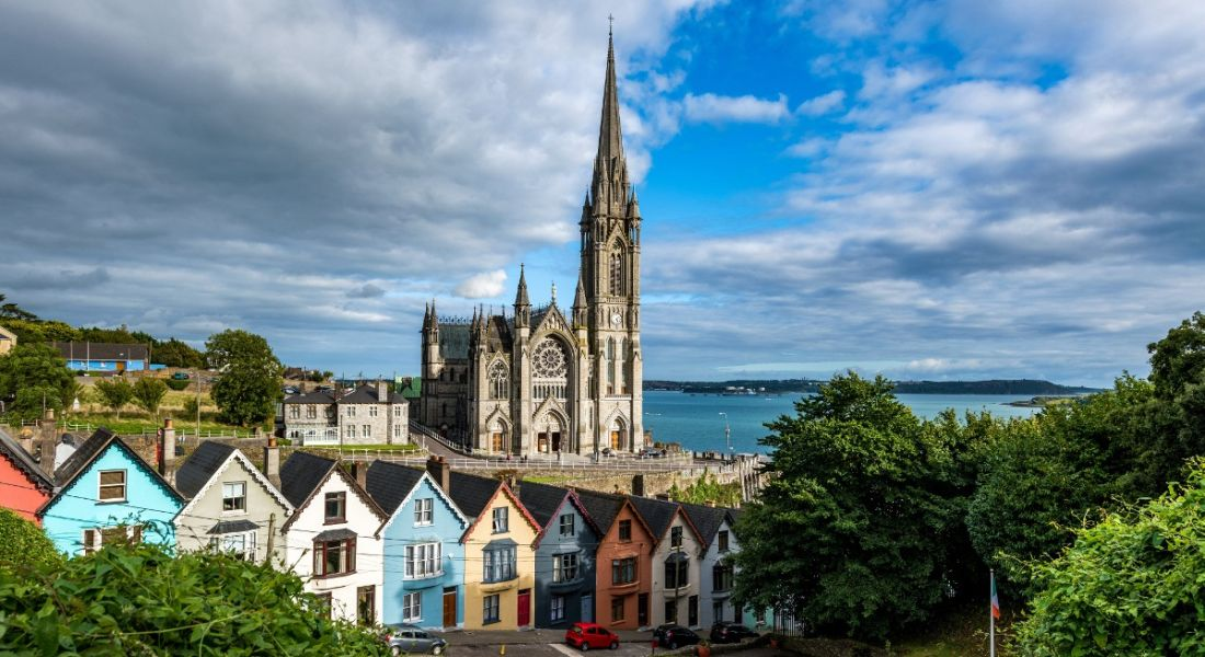 Photo of colourful houses in Cork, Ireland, with church spire in background.