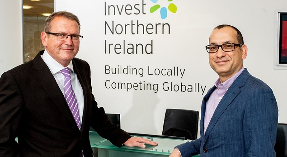View of two men in business attire standing in front of wall with Invest NI logo.