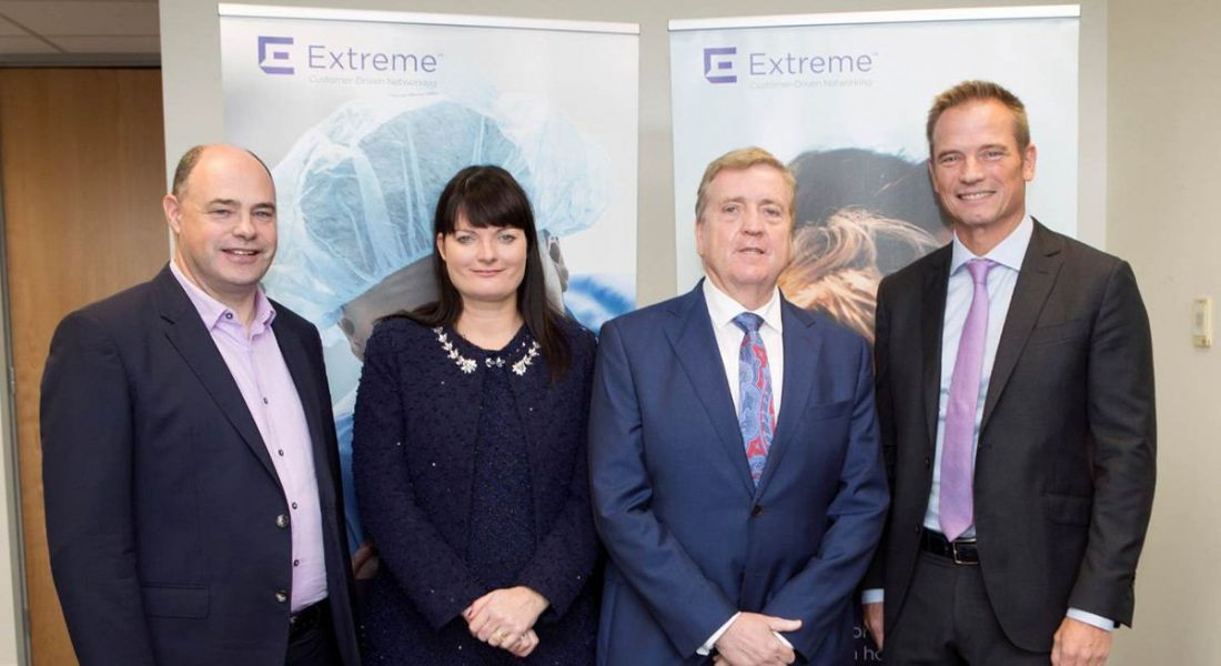 View of people in business attire standing in front of purple Extreme Networks logo.