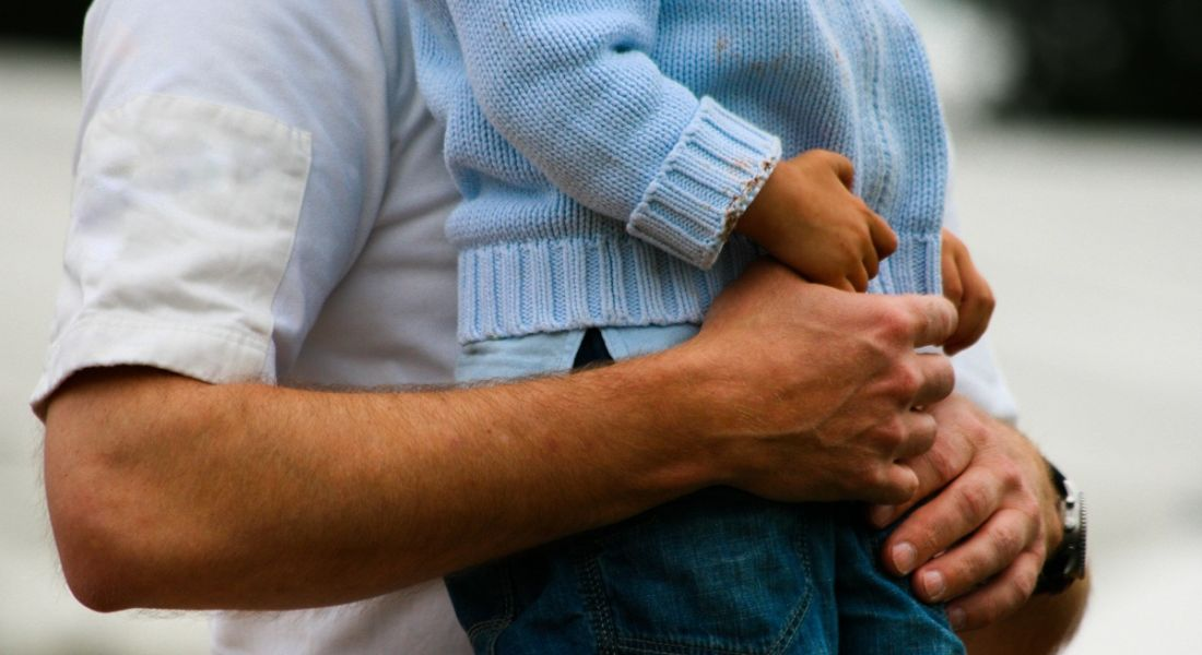 Photograph of a man holding a small child, showing only the midriff.