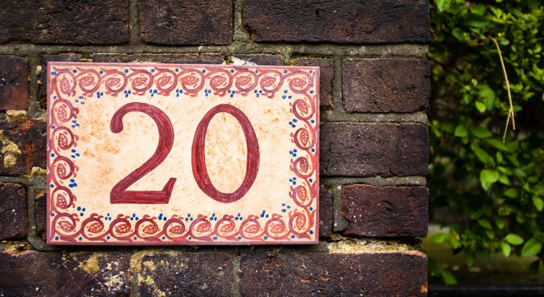 Hand painted number 20 tile on brick wall.