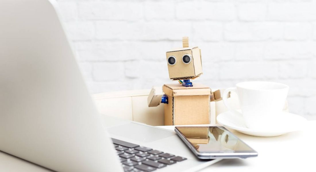 Robot sitting at a table and drinking coffee while working on a computer.