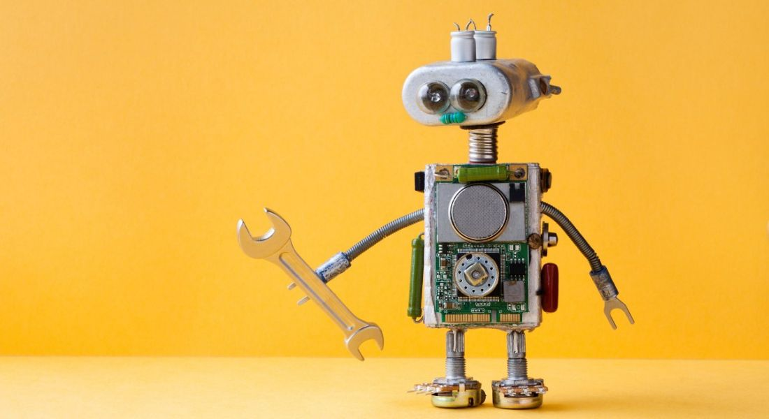 Small toy robot holding a spanner against a yellow background.