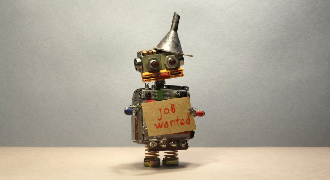 Toy robot with a cardboard sign and handwritten text saying Job Wanted against grey background.
