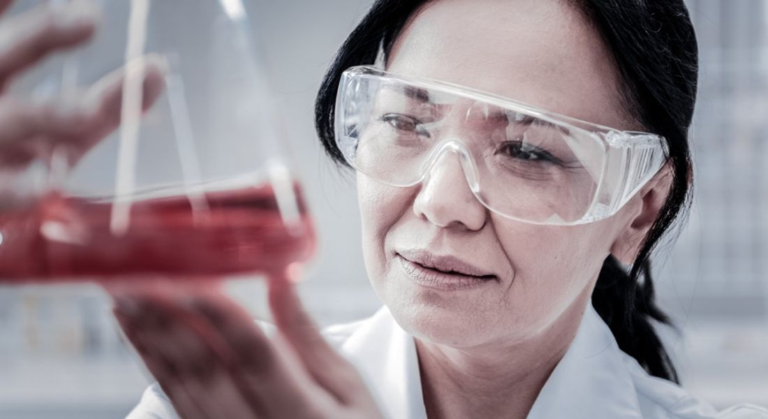 A close-up photo of a women holding up a scientific flask containing a red liquid in a lab setting.