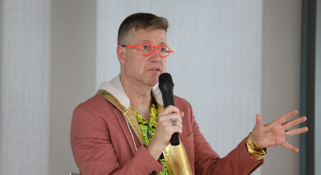 Man in highlighter orange framed glasses and salmon coloured blazer holding microphone and giving an address.