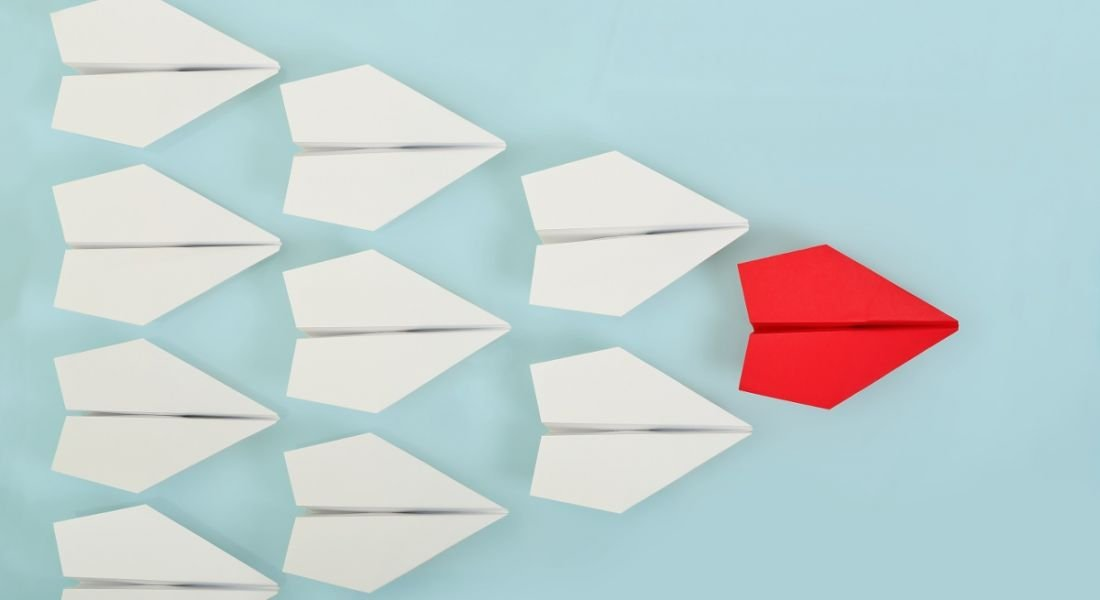 Red paper plane leading white ones, all placed against a light blue background.
