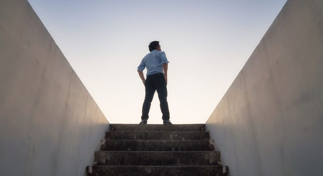 Person standing confidently at the top of a staircase to outside against a setting sun.