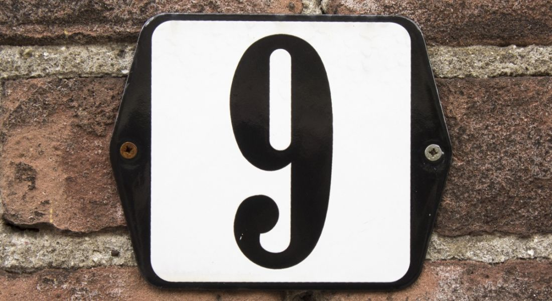 Enamelled number sign on the front of a house, displaying the number nine in black lettering on a white background.