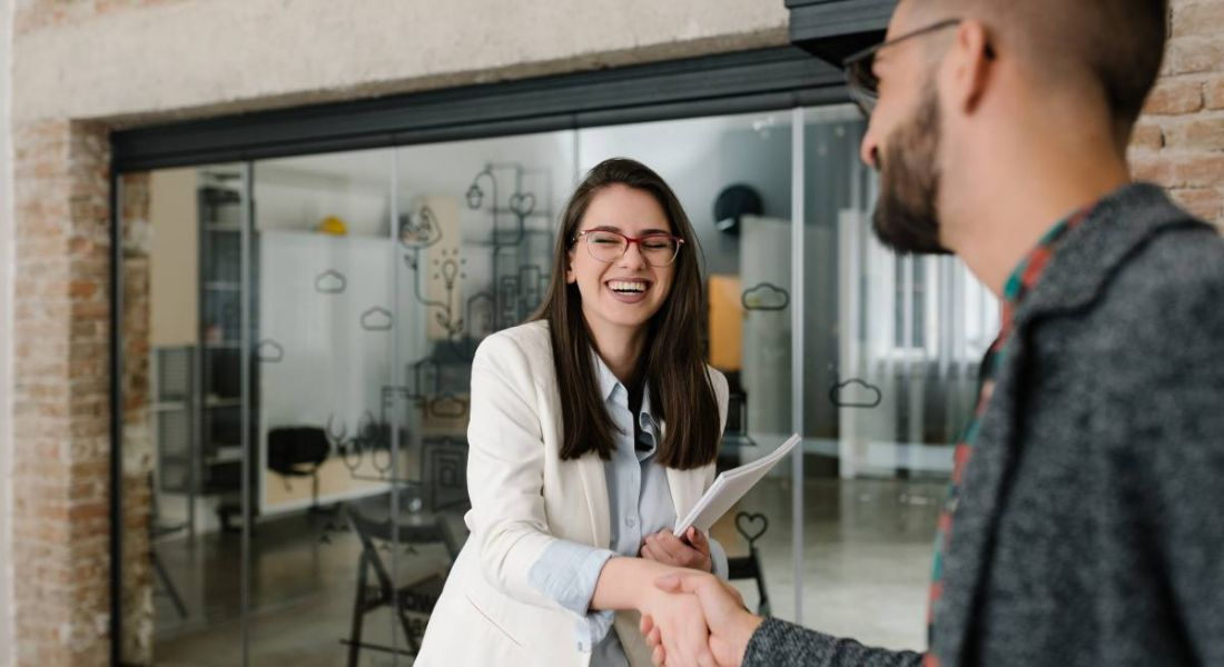 A woman shaking hands with a man and smiling. They are starting a very positive onboarding process.