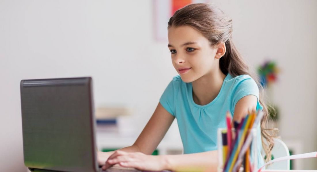 A young girl sitting at desk with a laptop in front of her, possibly playing a game about cybersecurity.