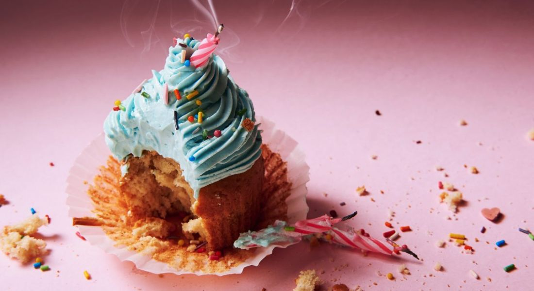 A gouged birthday cupcake with an extinguished candle sitting lopsided in the icing against a pink background.