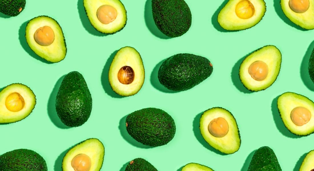 A variety of avocado halves, some with flesh turned up and others with skin turned up, against a green background.