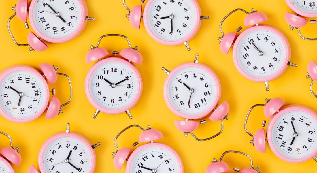 A series of pink old-style alarm clocks showing various times evenly spaced out against a yellow background.