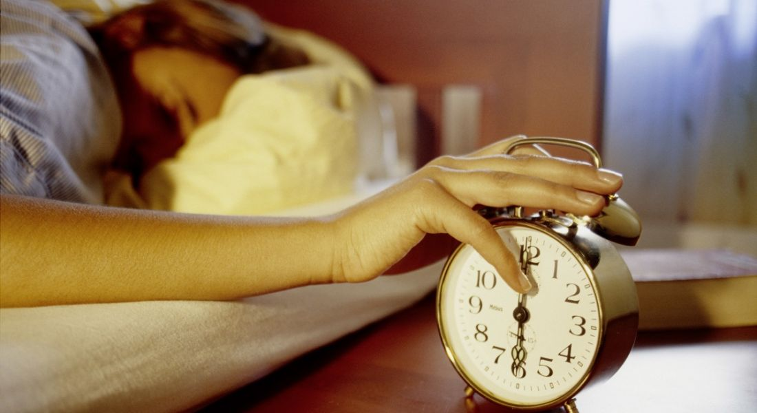 view of a sleeping person with their hand slapping an alarm that is shocking them into consciousness.