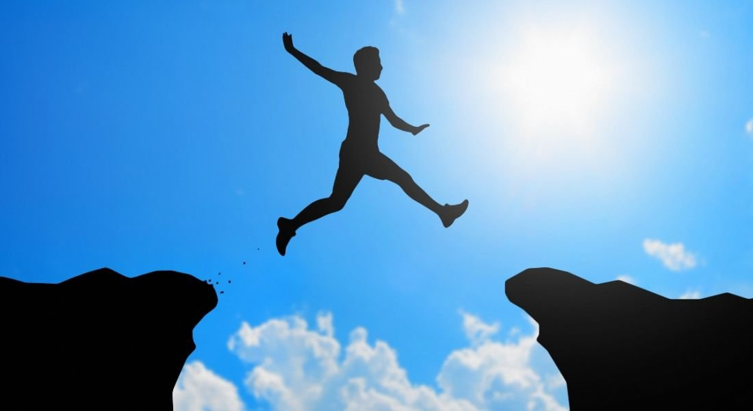 A silhouette of a man jumping from one cliff to another against blue sky to represent job-hopping.