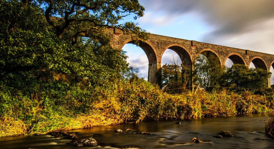 An arch bridge at sunset with a river in the foreground. It is in County Armagh, where Boyce Precision Engineering is.