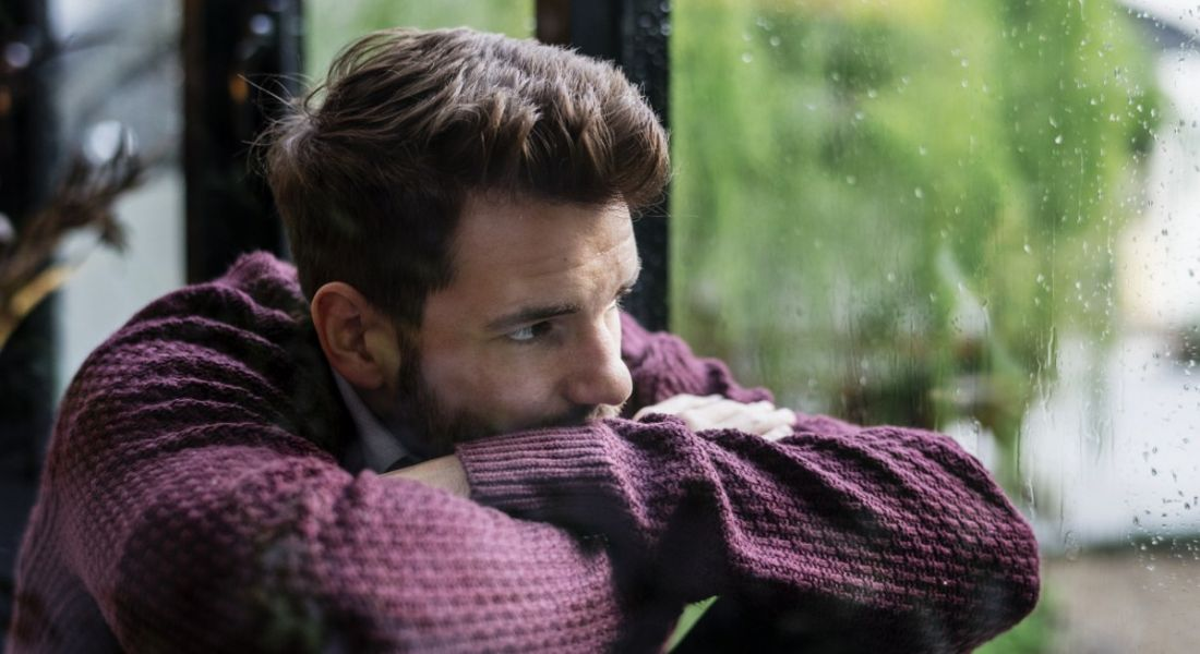 A man in a jumper with his head resting on his arms looking out the window at the rain. It's Blue Monday and he looks sad.