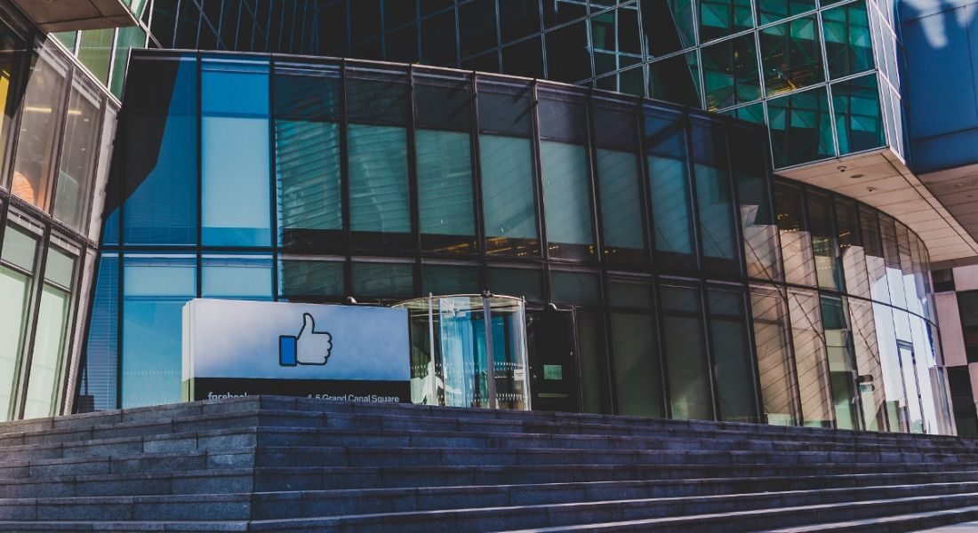A view of the glass exterior and concrete steps leading up to the Facebook offices in Dublin on a clear day.