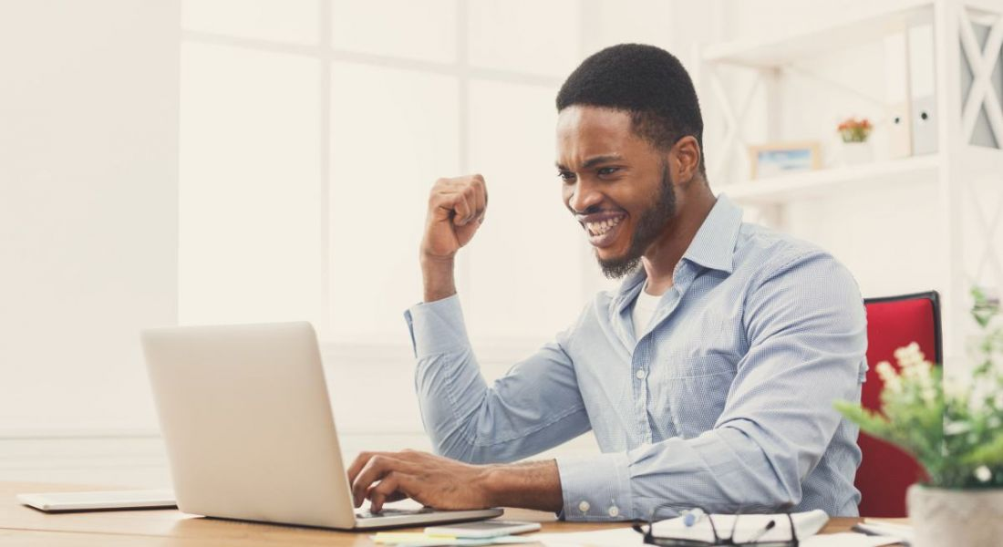 An excited man on a laptop with one fist in the air cheering. He's excited about getting a new job.
