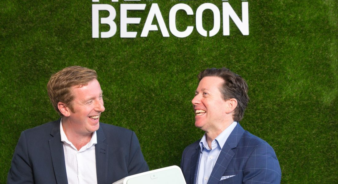 Two men in dark jackets sit before a green wall holding a white medical device in front of a green wall with HealthBeacon branding in white.