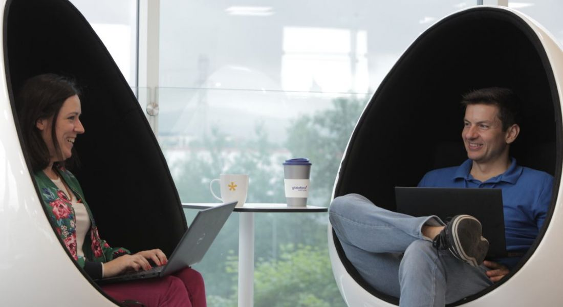 Two Globoforce employees, one male and one female, sitting in egg chairs facing each other. They have laptops on their lap.