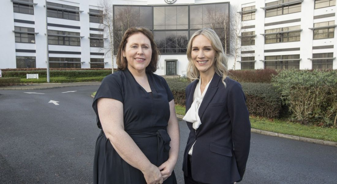 Two women in dark business attire smiling at camera against backdrop of Three Ireland building in Limerick.