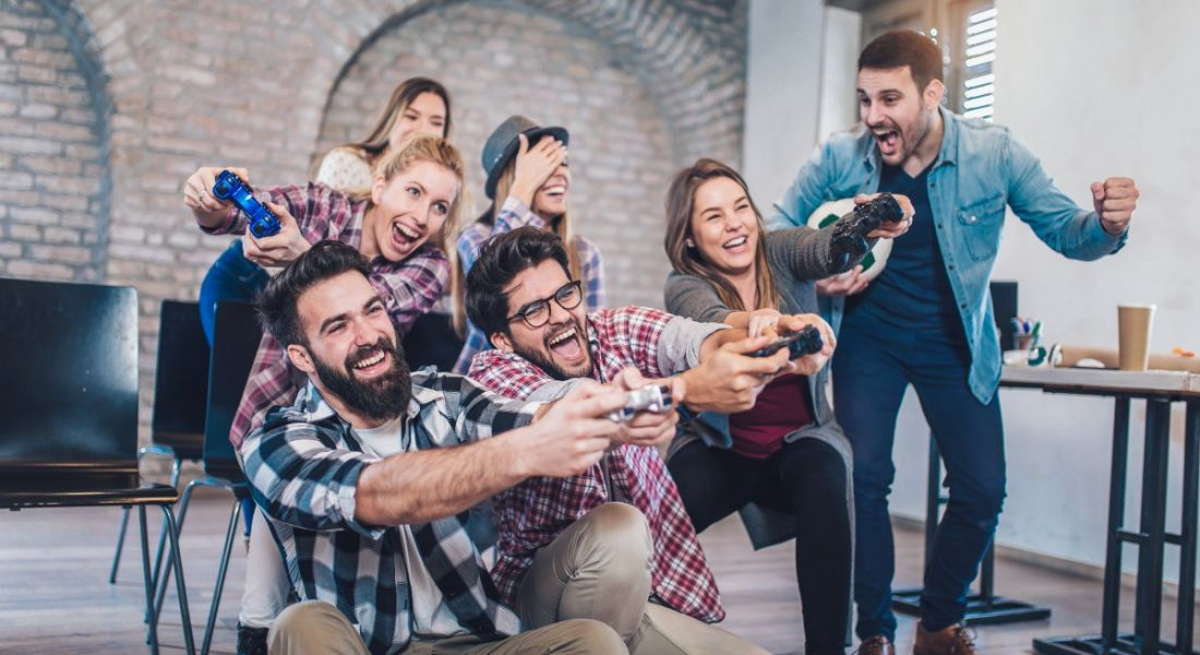 Diverse group of workers playing video games in an office and cheering with excitement.