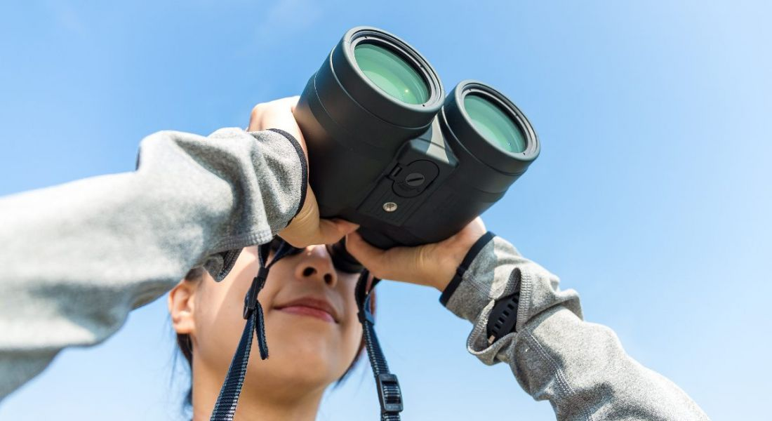 A close-up of a woman with binoculars against a blue-sky backdrop. It represents looking ahead to workplace trends in 2019.