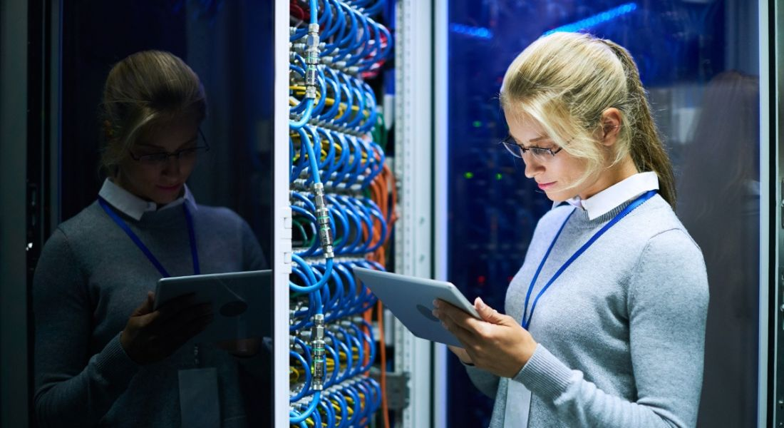 Blonde, female mainframe worker checking a tablet while standing beside a supercomputer full of blue wires.