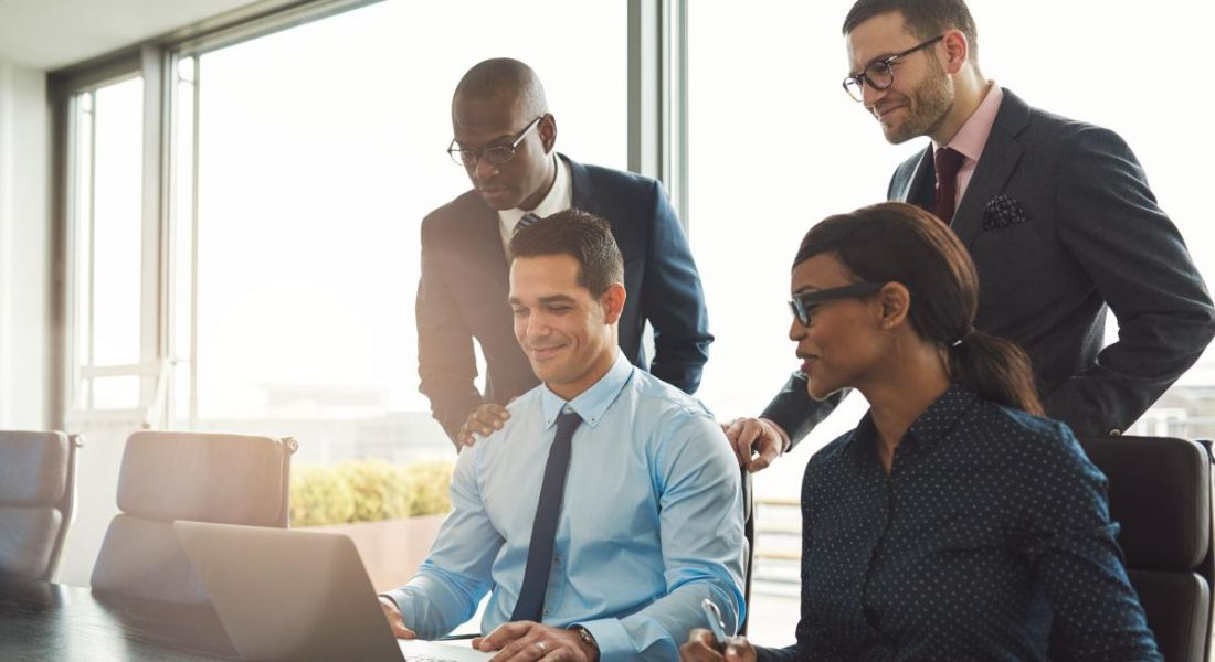 A diverse group of employees in a boardroom smiling and looking at a laptop.
