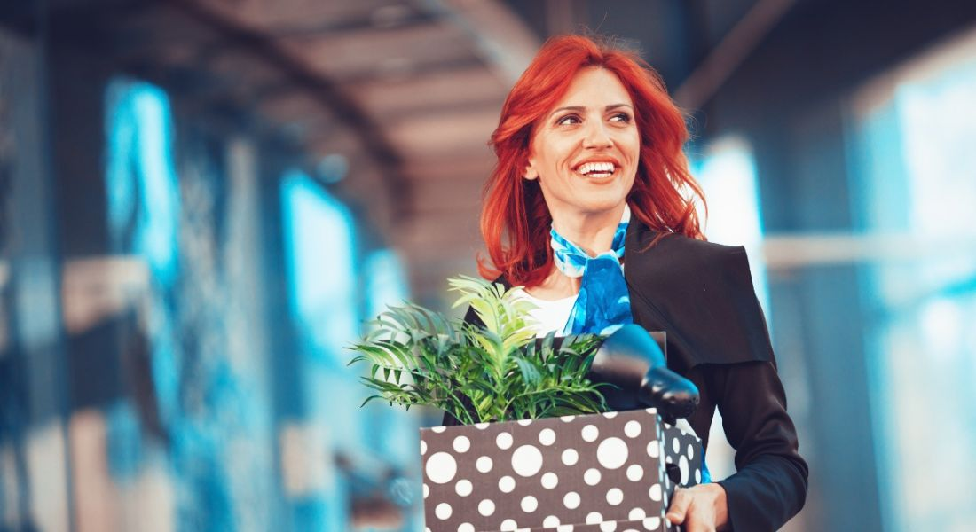 A smiling red-haired business woman holding a box of office supplies. She symbolises leaving your job.